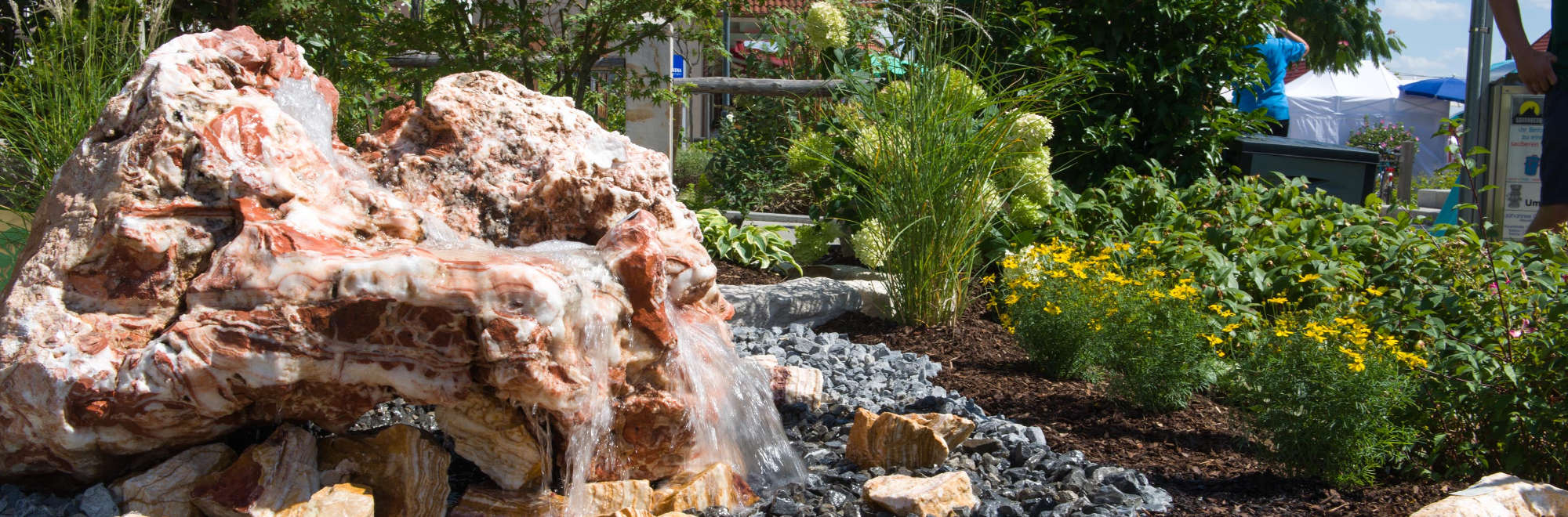 Gartenmarkt, Stein mit Wasser und Bepflanzung